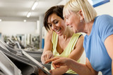 Fototapety Female fitness trainer is discussing program with woman on a tre