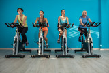 Fotoroleta Four women are cycling at the fitness center