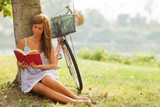 gorgeous woman is reading a book next to a tree where her bike i