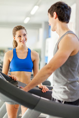 Female fitness instructor smiling towards young man on a treadmi