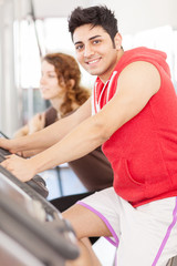 Young adult man looking at the camera while doing workout on the