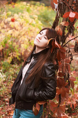 Girl in autumn leaves. Portrait of beautiful brunette