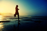 Fototapeta young woman running on sunrise beach