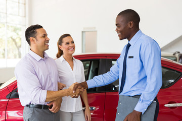 car salesman handshaking with middle aged buyer