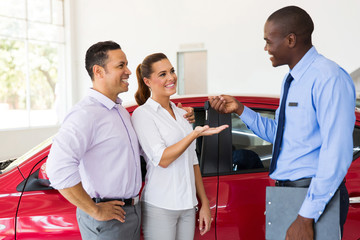 car salesman handing over new car key to couple