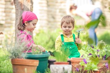 Two cute little children planting flowers