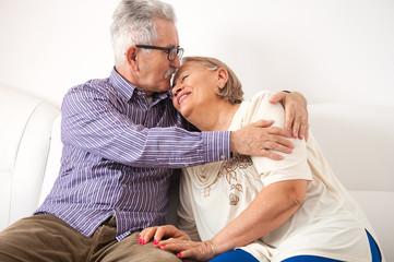Loving senior couple enjoying the embrace on the couch