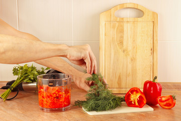 Hands cook put chopped fresh herbs in a blender