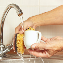 Hands with sponge wash coffee cup under running water