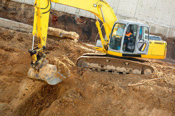 Excavator with metal tracks loading soil at construction site