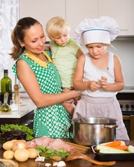 Mother with two daughters cooking