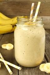 Banana oatmeal breakfast smoothie in mason jar on wood