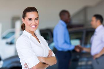 young saleswoman standing inside vehicle showroom