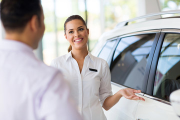 saleswoman showing new car to a customer