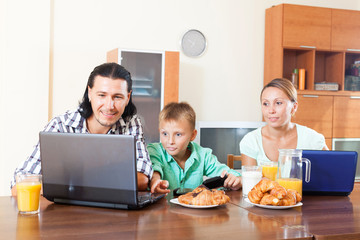 ordinary couple with teenager son using devices during breakfast