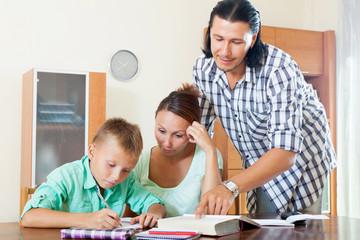 schoolboy and parents doing homework together