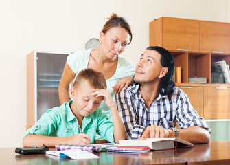 couple with teenager son doing homework