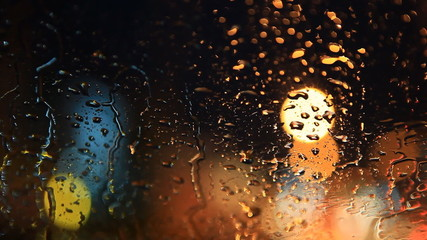 rain flows on the front windshield of car, blurry traffic lights