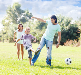 couple with boy playing with soccer ball