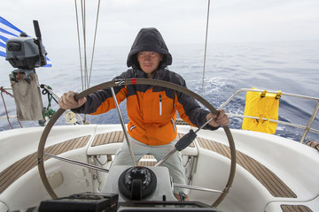 Young man skipper in the sea at the helm of a sailing yacht.