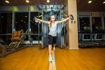 Young attractive woman does crossfit push ups with trx fitness