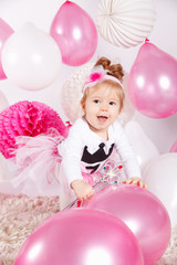Happy baby girl playing with balloons