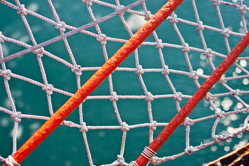 Orange stripes and rope net over turquoise ocean