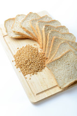 whole wheat bread and wheat grains on white background