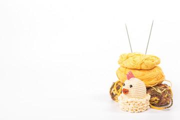 Knitted chicken on background wooden yarn