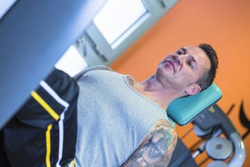 man making leg press exercise - workout routine .