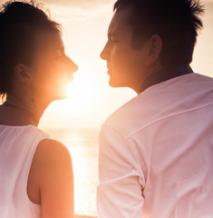 Young couple at sun background