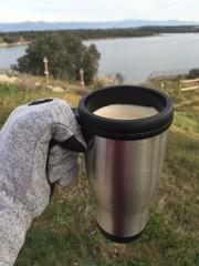 reponiendose del frio con un cafe en la naturaleza