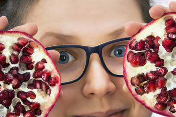 Smiling young woman with eyeglasses and pomegranate