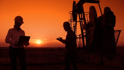 Oil pump jack and two oil workers at sunset, teamwork