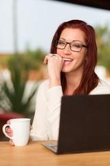 Junge Frau mit Brille am Laptop macht Kaffeepause