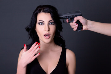 young beautiful terrified woman hostage and male hand with gun o