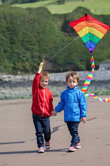 Two children playing with a kite on the beach