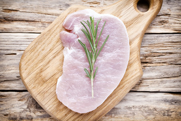 Pork chop, meat slices  on a wood background.