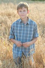 Teenage farmer standing among field of barley