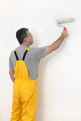 Worker painting wall in a room, home renovation