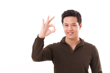 handsome, happy, smiling man giving ok hand sign studio shot