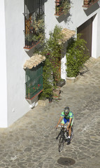 Bicycle rider on a traditional spanish rural street. Cadiz
