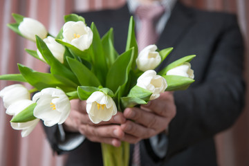 Businessman in a suit gives a bouquet of flowers