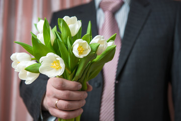 Man - businessman in a suit gives a bouquet of flowers, white tu