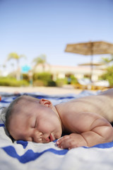 little girl sleeping on a towel on palm trees