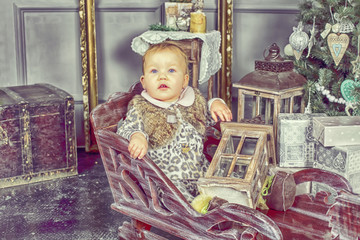 beautiful baby stands near a wooden sled in the studio cones