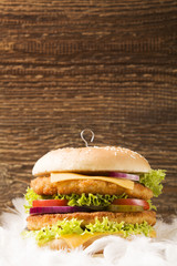 Chicken burger with cheese, lettuce, tomato and onion in feather