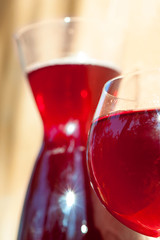 Glass of homemade red wine with carafe on stone wall background