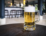 Glass of Beer on table with Blurred Bar counter background