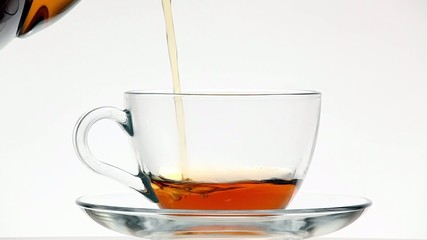 Hot tea flowing to tea cup on a white background